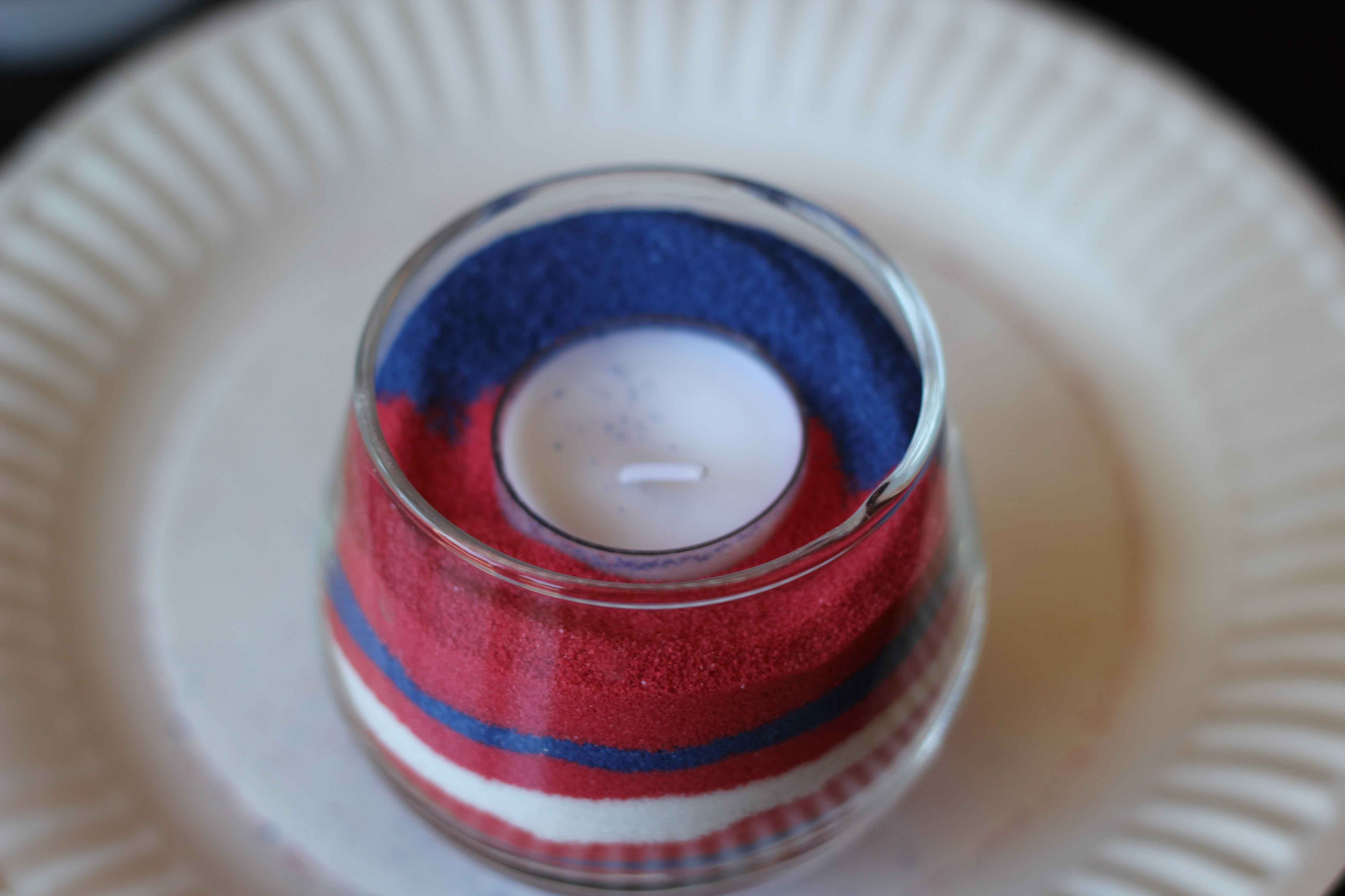 #DIY Sand Candles - I love these! I used drinking glasses and a votive I bought from a thrift store, added the #sand and a tea #candle. 30 minutes later I have 4 great candles for #4th of July. Made all four candles for $8 bucks! This pin was tested and reviewed by one of the 3 crazy sisters at https://www.thisgrandmaisfun.com/