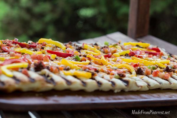 Grilled Flat Bread with Chorizo and Peppers - If you have never made bread on the BBQ you have been missing out! You can make this flat bread with refrigerated pizza dough and be done start to finish in 15 minutes. The BBQ gives this bread the perfect combination of flavors.