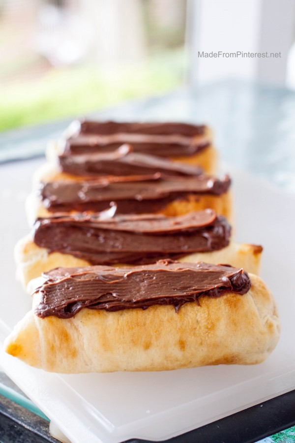 Campfire Eclairs  - Once the shells are made, cooled and filled, a generous swipe of chocolate frosting is the next to last step for a campfire dessert that tastes as good as it looks!