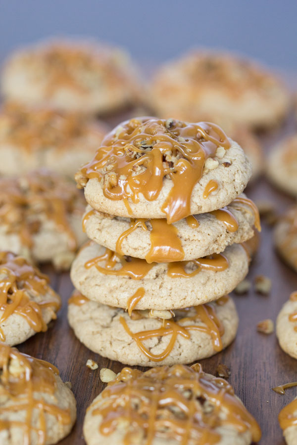 Apple Caramel Cookies - There is a secret ingredient that gives these moist cookies their sweet tangy apple flavor! Stuffed with caramel, topped with walnuts and drizzled with a little more caramel. Best fall cookies EVER!