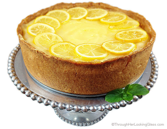 Spectacular Lemon Bar Cheesecake. Deliciously sweet and crunchy crust, creamy cheesecake and tangy homemade lemon curd. All garnished with tart candied lemon slices.