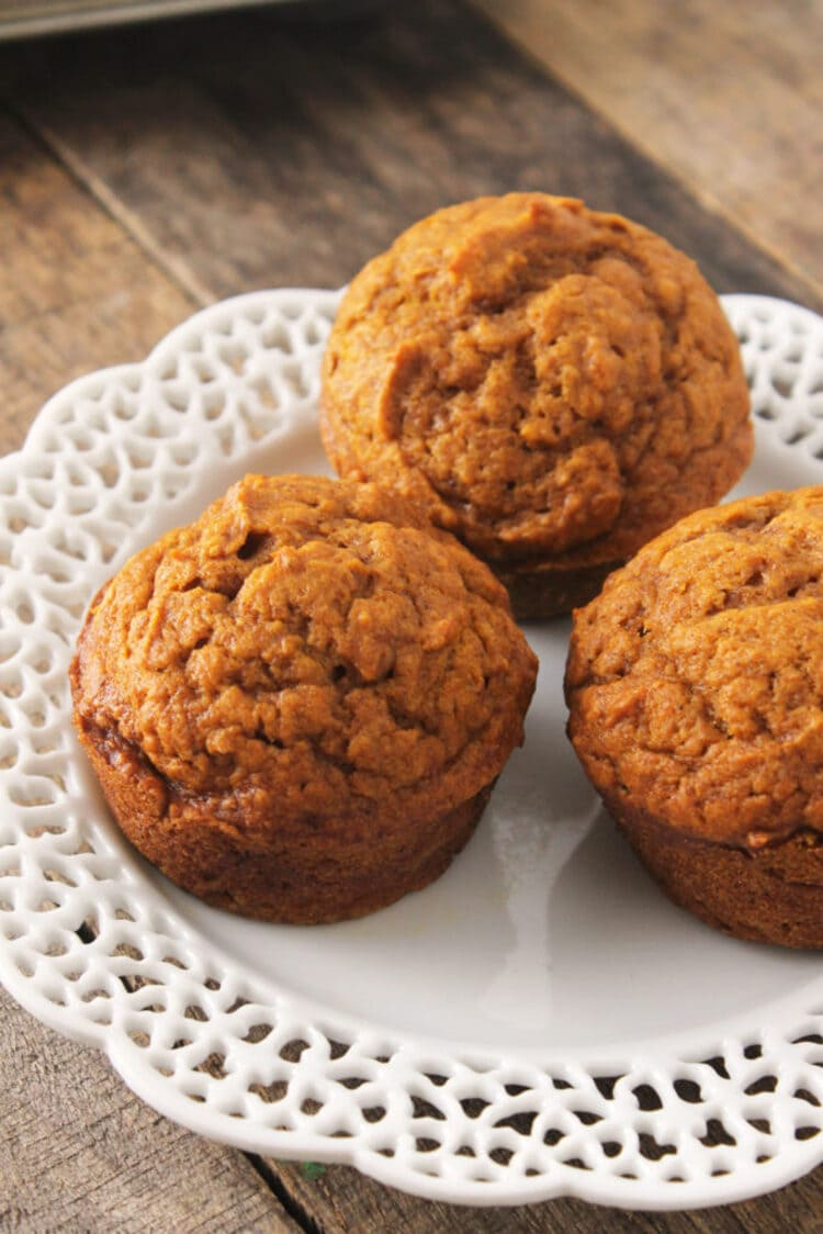 Three ready to eat pumpkin muffins displayed on a white plate