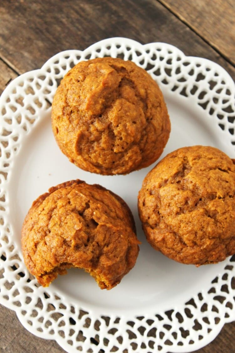 Close up photo of three ready to eat muffins on a white plate with one muffin having a bite mark