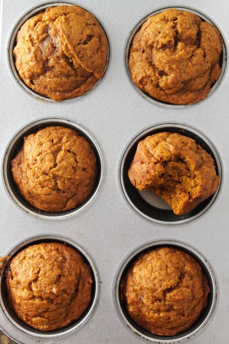 Six ready muffins in a baking tin with a bite on one muffin