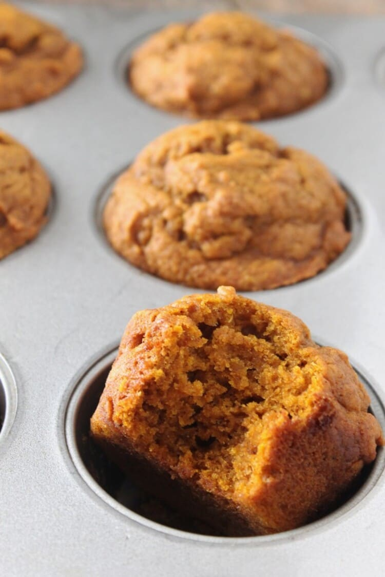 Close up photo of muffins in a baking tin with one with a bite