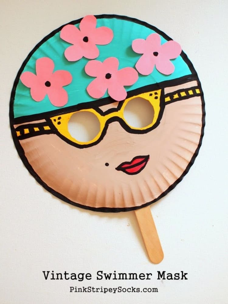 Paper plate craft swimmer mask with yellow sunglasses and red lipstick on a white background
