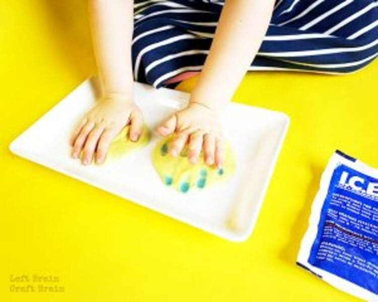 science project color changing slime, two hand touching a color changing slime on a yellow background