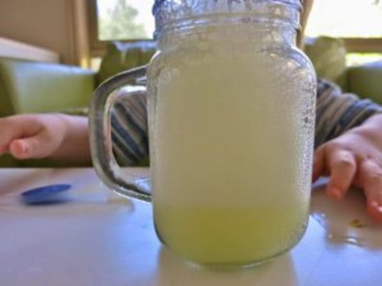 science project fizzing lemonade in a transparent glass on a table