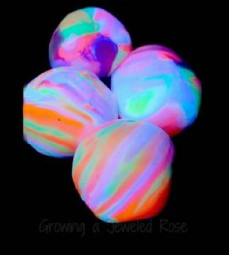 science project for kids four glowing balls in the dark in bright neon colors on a black background