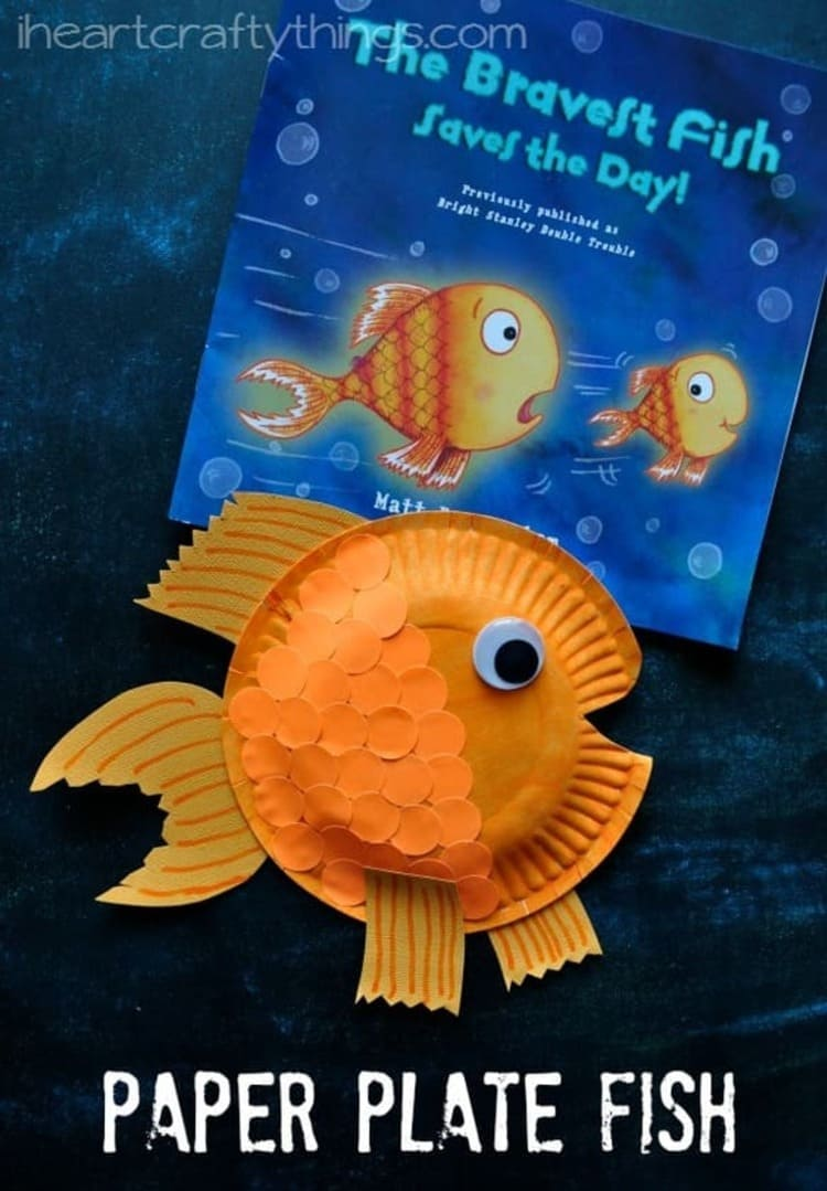 paper plate craft orange fish with a book next to it on a dark blue background
