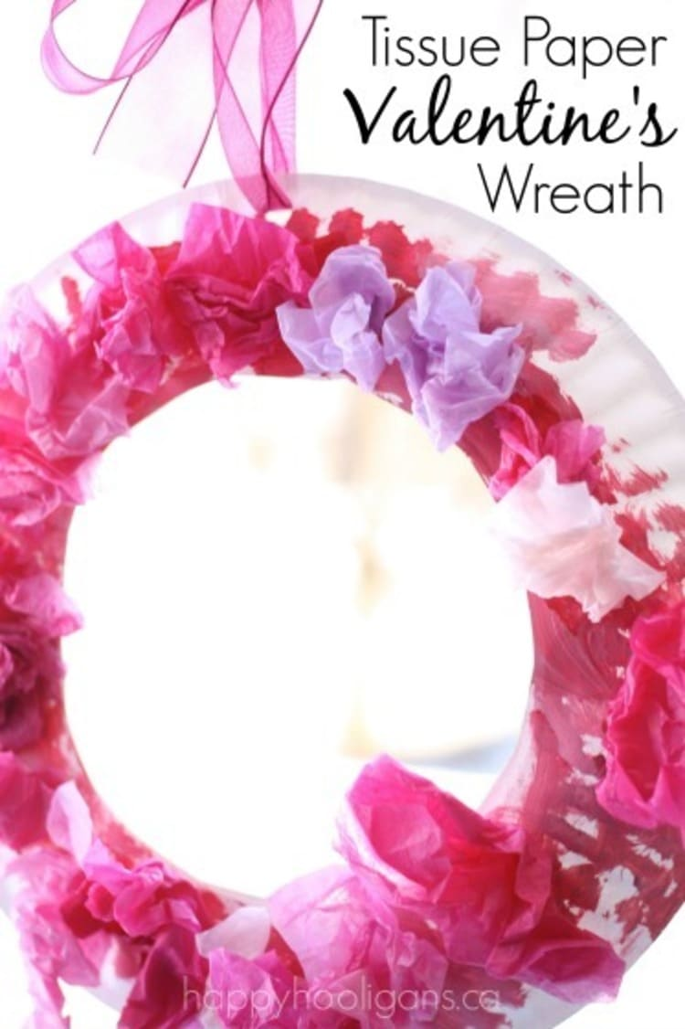 paper plate craft valentine`s day wreath in red and pink colors on a white background