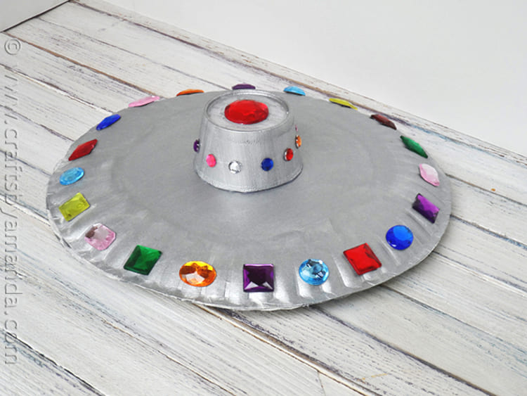 paper plate craft flying saucer with gems of different colors on wooden background
