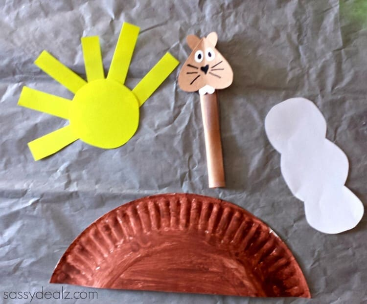 paper plate craft groundhog day with a sun and a cloud on a grey background