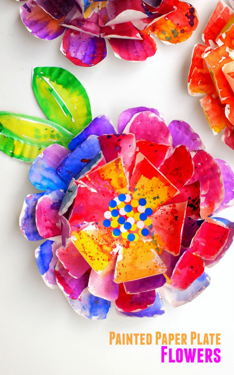 paper plate craft painted flower in red, blue, purple, yellow with green and yellow leaves, on a white background