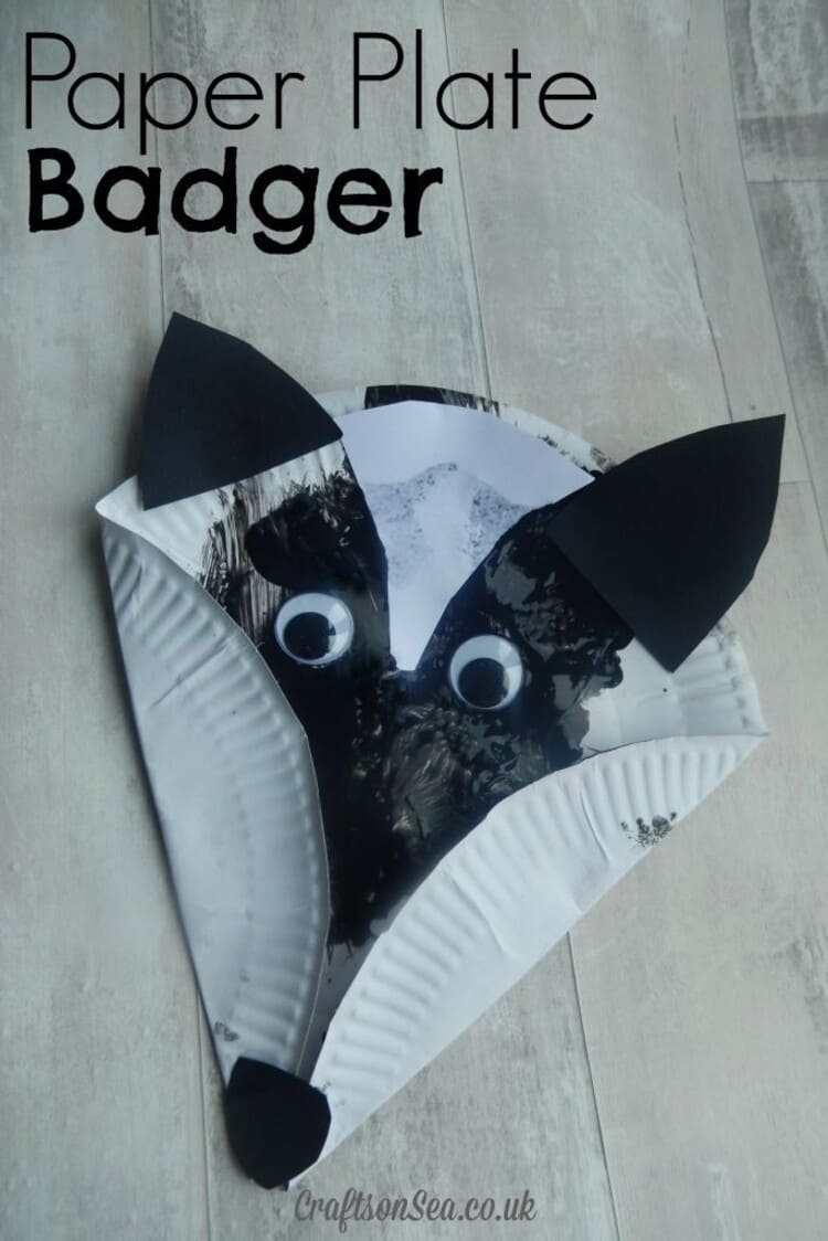 paper plate craft black and white badger on a light wooden background