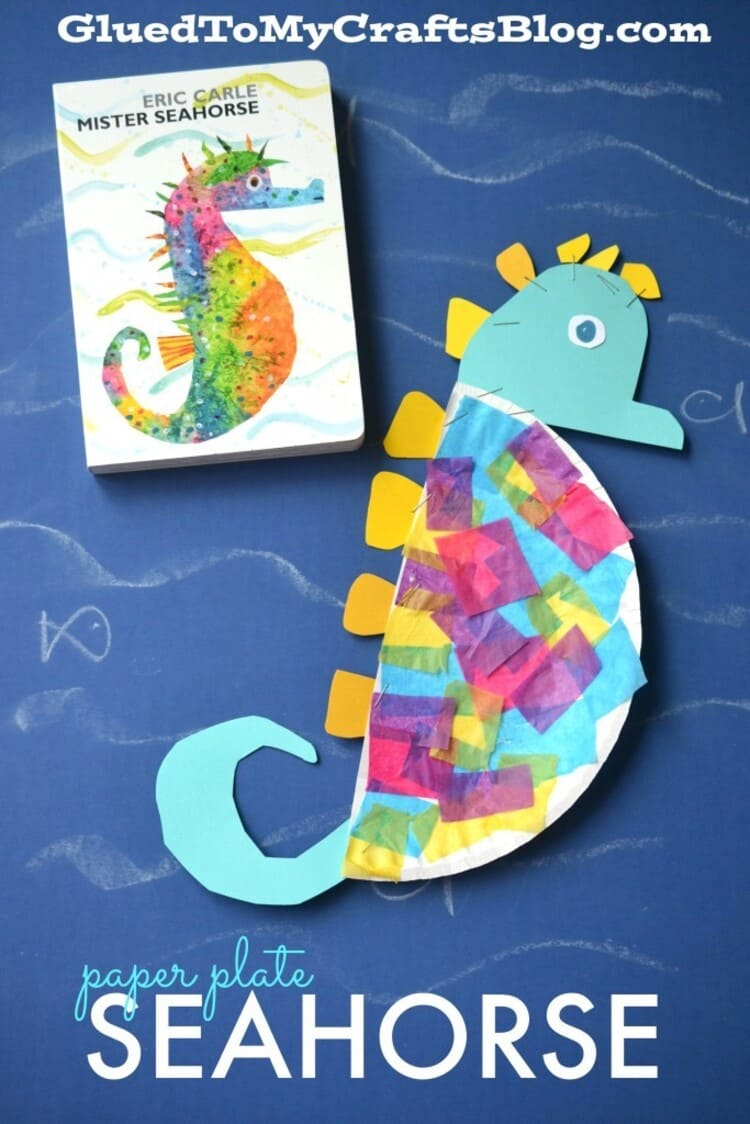 paper plate craft seahorse and a book next to it on a blue background