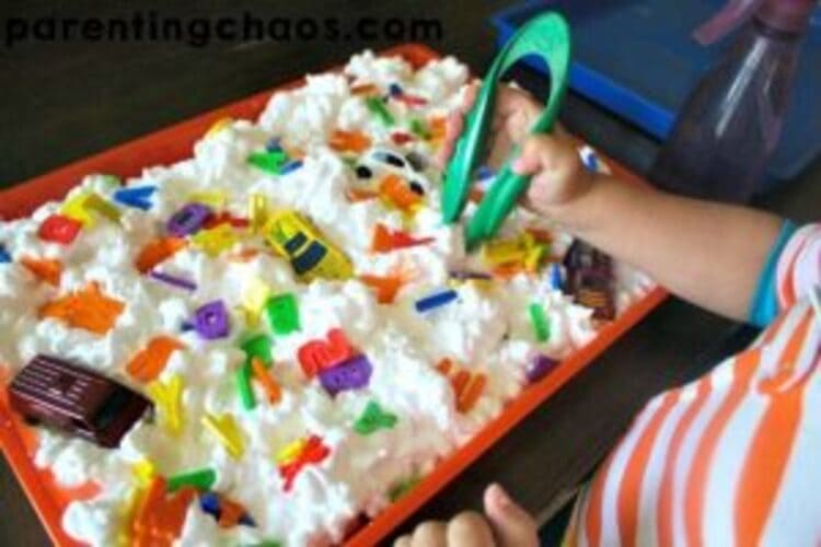 ABC Carwash sensory play - A photo of a child playing in a bin full of shaving cream and letters of the alphabet