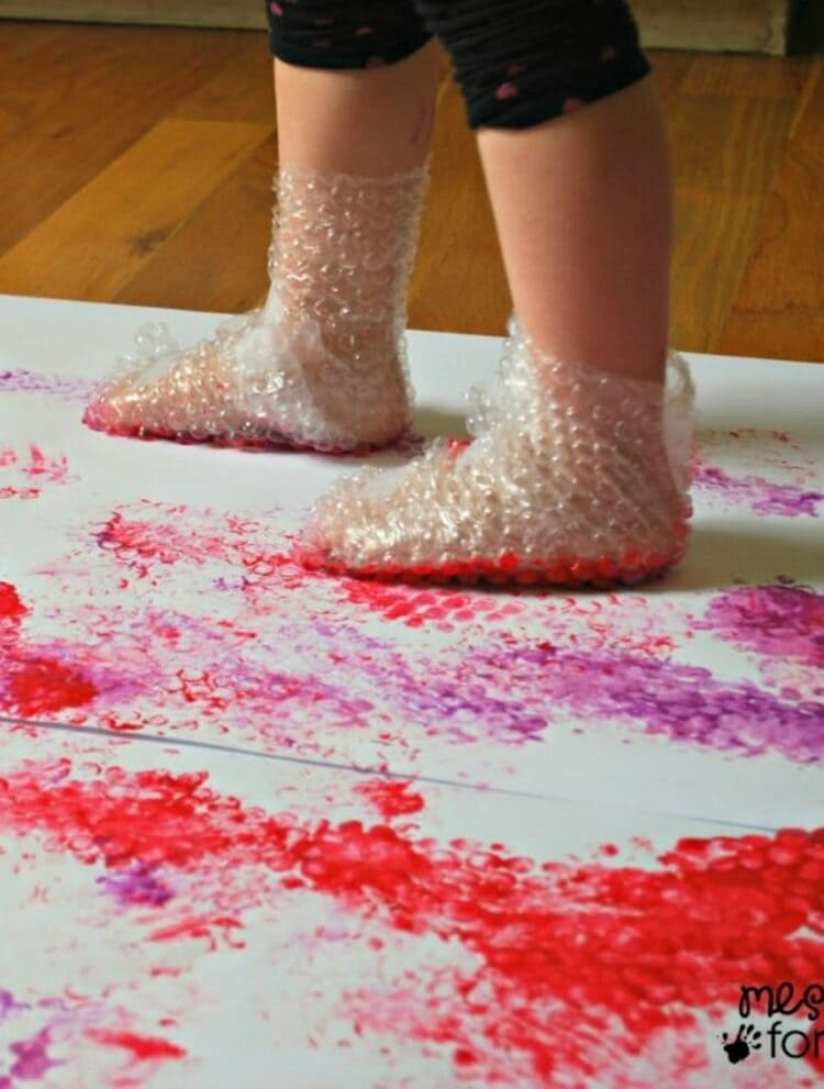Little legs covered in bubble wrap stomping on paint