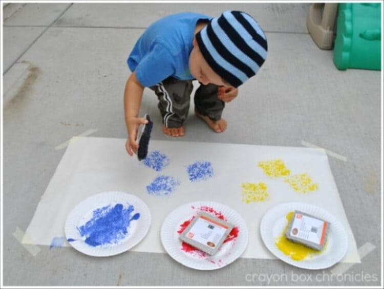 Creative sensory play - A child using carpet squares to paint on canvas on the floor