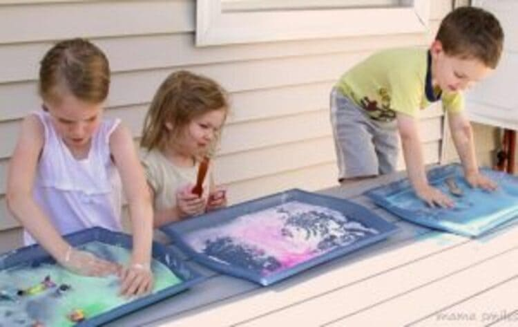A photo of three children cornstarch painting on trays with their hands