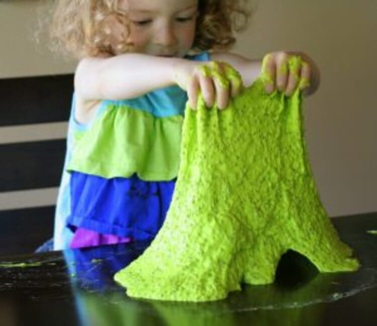 Edible slime sensory play - a photo of a little girl playing with edible slime, pulling it off the table