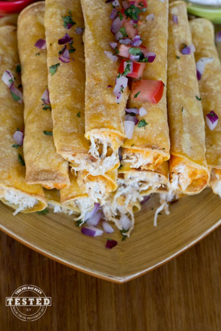 Crockpot Cream Cheese Taquitos - pyramid pile of creamy cheesy taquitos with salsa and onions on top
