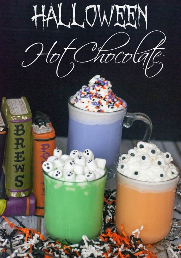 Neon Colored Halloween Hot Chocolate with spooky toppings near spell books