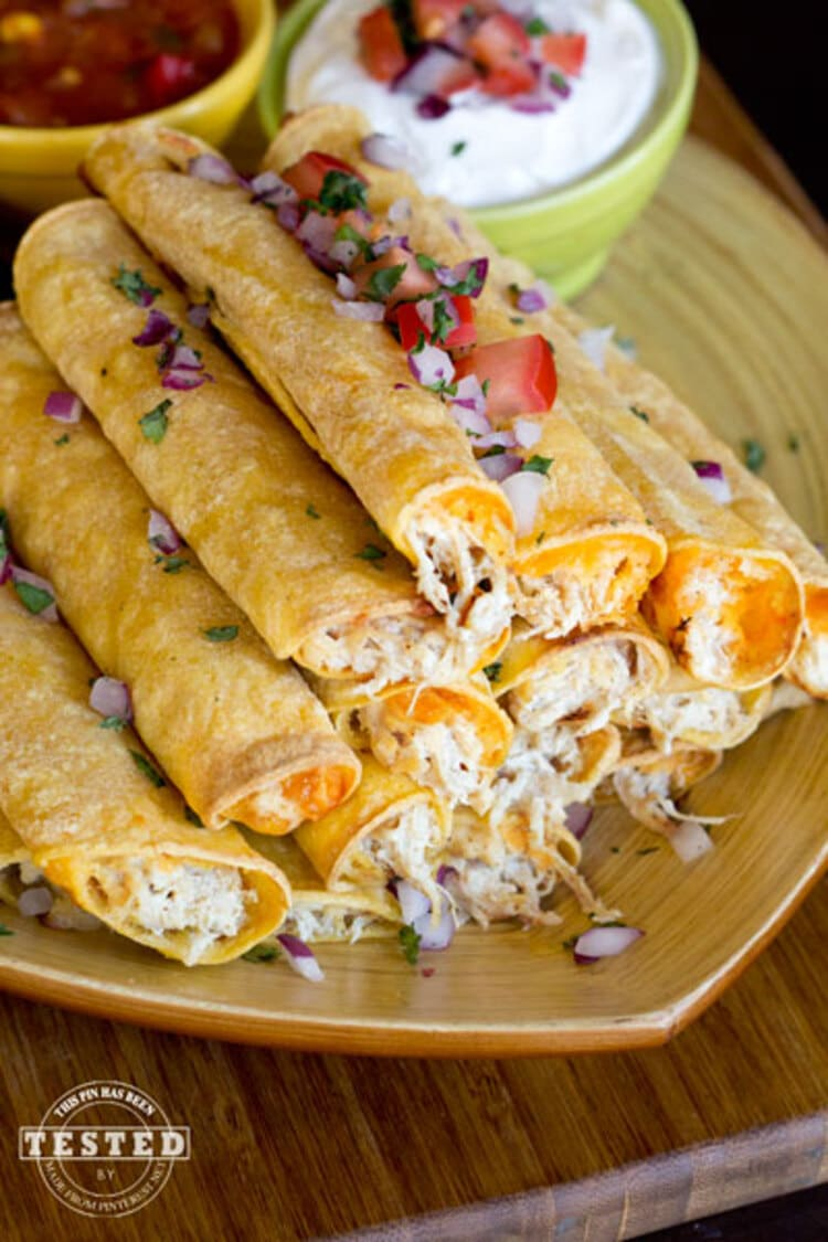 Crockpot Cream Cheese Taquitos - pile of tightly rolled up cheese and chicken taquitos with sour cream and salsa dip on the side