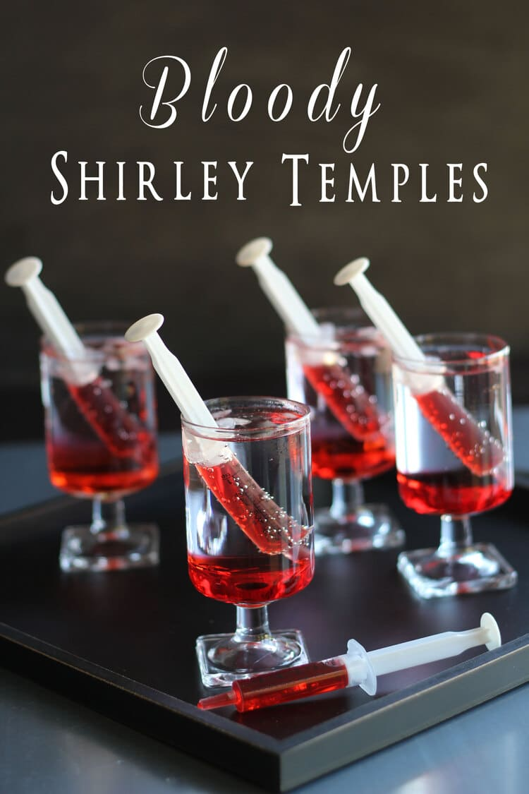 Four glasses with ready to drink Shirley Temple drink with each glass having a syringe with grenadine syrup in it.