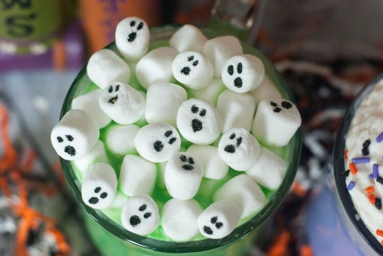 White Marshmallow ghosts atop a spooky green mug f Halloween hot Chocolate