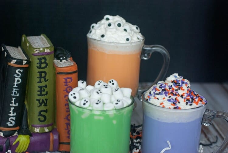 Spooky colored Halloween Hot Chocolate in darling mugs with festive treat toppings.
