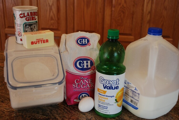 ingredient list on a worktop: Flour tub, with butter stick and baking powder on top, bag of cane sure, 1 egg and lemon juice bottle and a large bottle of milk.