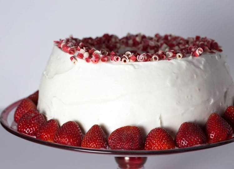 Full strawberry filled angel filled cake placed on a plate