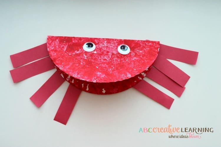 paper plate craft red ocean crab with eight legs and eyes, on a light background