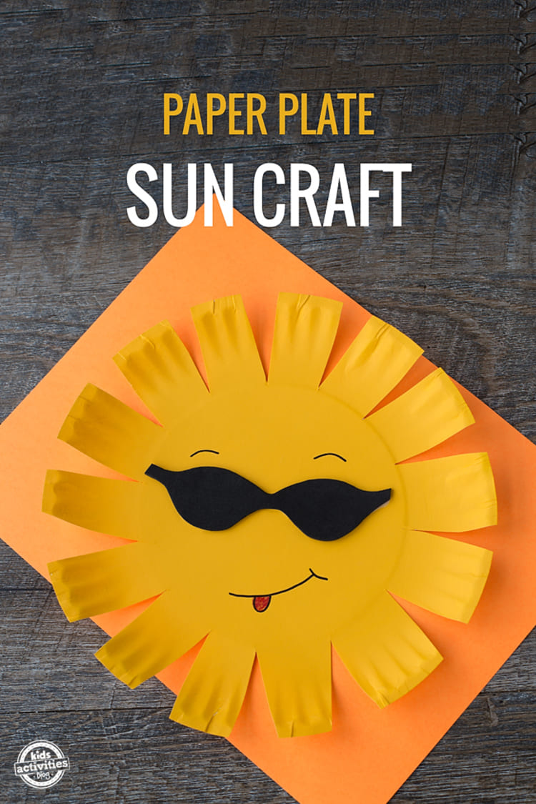 Paper plate craft yellow sun with black sunglassess smiling and showing tongue on a yellow paper sheet with black wooden background