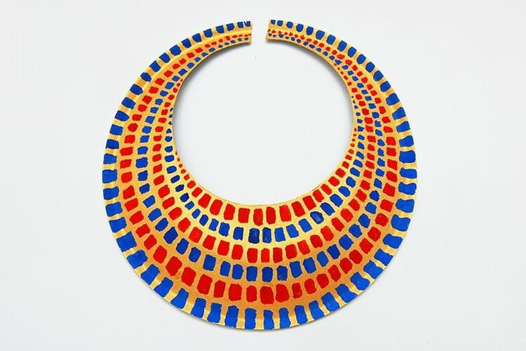 paper plate craft eqyptian necklace with red and blue colors on a white background