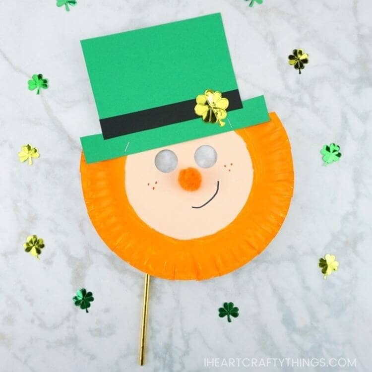 paper plate leprechaun mask with a green hat and an orange beard smiling on a marble background