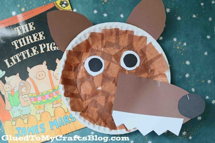 paper plate brown craft wolf on a green background next to the book The Three Little Pigs